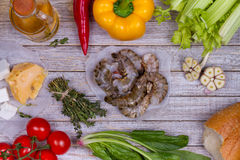 Delicious fresh shrimps and vegetables on wooden background. Stock Images