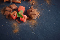 Delicious fresh slices of watermelon with cinnamon and chocolate. On the dark background Royalty Free Stock Photo