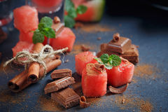 Delicious fresh slices of watermelon with cinnamon and chocolate. On the dark background Royalty Free Stock Photos