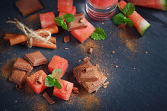 Delicious fresh slices of watermelon with cinnamon and chocolate. On the dark background Royalty Free Stock Images