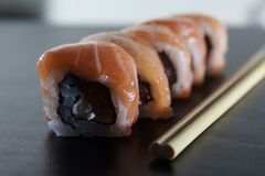 Delicious fresh sushi rolls with salmon and cream cheese on black plate. Traditional japanese food, healthy food concept.  stock photos