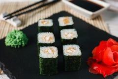 Delicious fresh sushi rolls served on black slate stock photos