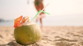 Delicious Fresh Thai Coconut Cocktail with Young Tourist Girl in Bikini Running Barefoot at Tropical Beach on Background. 4K, Slowmotion. Phuket, Thailand stock footage