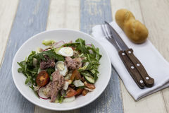 Delicious fresh vegetable salad with tuna on white porcelain plate with fork and knife. Stock Images