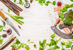 Delicious fresh vegetables, spices and seasoning for tasty cooking with kitchen knife on white wooden background, top view, frame. Healthy  clean or vegetarian Royalty Free Stock Photo