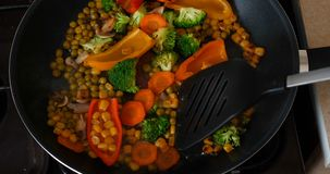 Delicious fresh vegetables are stewed in a pan, food for vegetarians at home. Concept of: Veg, Bio Product, Mushrooms, Broccoli, Colored Cabbage, Carrot, Corn stock footage