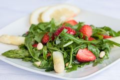 Ready to eat. Healthy eating concept. Vegetable salad. Delicious fresh vegetarian salad with asparagus, strawberries and arugula. Diet food Royalty Free Stock Images