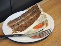 Delicious freshly baked cooking carrot cake slice homemade baking. Photo of a freshly baked homemade carrot cake slice with carrot decoration and icing royalty free stock photos