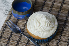 Delicious freshly baked cupcake. With decorative twirled white icing served with a fork on a placemat, high angle view Royalty Free Stock Photography