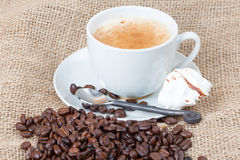 Delicious freshly brewed cup of coffee with whole beans on burla Royalty Free Stock Photography