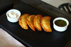 Delicious fried cheburek pies on the dark plate with two sauces Stock Photo