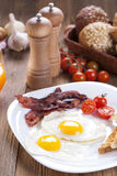 Delicious fried egg with spices, bacon, croutons and tomatoes on Stock Photography