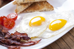 Delicious fried egg with spices, bacon, croutons and tomatoes on Royalty Free Stock Photo