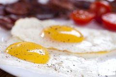 Delicious fried egg with spices, bacon, croutons and tomatoes on Royalty Free Stock Image
