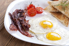 Delicious fried egg with spices, bacon, croutons and tomatoes on Stock Photo