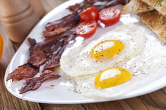 Delicious fried egg with spices, bacon, croutons and tomatoes on Stock Images