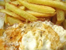 Delicious fried eggs with chips #2. Delicious fried eggs with chips, served straight off the frying pan, you can see the sizzling fat royalty free stock photography