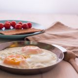 Delicious fried eggs in a frying pan. Appetizing breakfast. Eggling of the fried. There is a wooden spoon nearby. Cherry. Tomatoes on a blue plate. Blurred stock photo