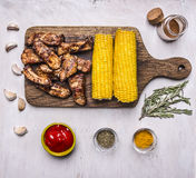 Delicious fried lamb ribs on a cutting board, with corn, spices, hot sauce on white  wooden rustic background top view close up Royalty Free Stock Photos