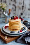 Fluffy pancakes on breakfast table with coffee in morning light. Close-up. stock photos