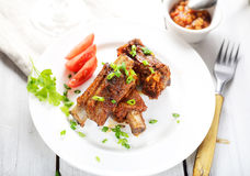 Delicious fried pork ribs on a plate, sauce, fork, greens Stock Images
