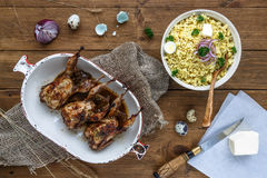 Delicious fried quails with eggs with bulgur porridge on a wooden table, rustic style. Top view.  Stock Images