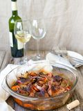 Delicious fried Quails with vegetables - garlic, carrots, onions , baked in a glass form, bottle of white wine and two glasses on. A rustic wooden background royalty free stock photo