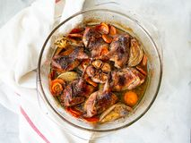 Delicious fried Quails with vegetables - garlic, carrots, onions , baked in a glass form with a light background. Dietary, gourmet. Lunch. Close up, selective royalty free stock image