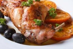 Delicious fried rabbit leg with oranges, macro. Horizontal Stock Photos