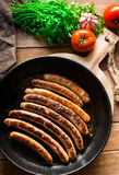 Delicious fried sausages with golden crust in iron cast pan, fresh parsley tomatoes Royalty Free Stock Photo