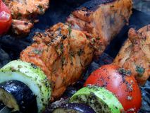 Delicious fried shish kebab with vegetables on a spit Royalty Free Stock Images