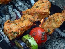 Delicious fried shish kebab with vegetables on a spit Stock Photo