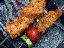 Delicious fried shish kebab with vegetables on a spit Stock Image