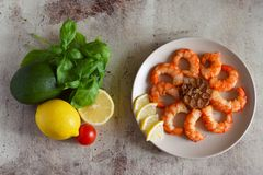 Delicious fried shrimp on a plate with garlic. Lemons, avocado, Basil and tomato on the table. stock image