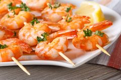 Delicious fried shrimp on wooden skewers close-up horizontal Stock Images