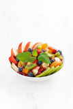 Delicious fruit and berry salad in white bowl, vertical Stock Image