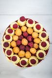 Delicious fruit cake with raspberries and cream, on a blurry background. Vertical frame Stock Photography