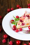 Delicious fruit cake on white plate. Vertical photo of white plate with single portion of fruit pie. Several raspberries and cherries are around with single fork royalty free stock image