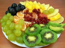 Delicious fruit salad. Kiwi fruits, oranges, mango, apples, grapes, pomegranate, grapefruit  and avocado Stock Images