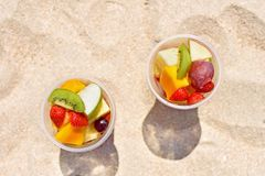 Delicious fruit salad in plastic cup on beach. Delicious fruit salad in plastic cup on summer beach stock photography