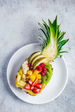 Delicious fruit salad served in fresh pineapple on white plate. Top view Stock Photo