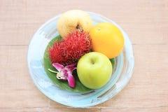 Delicious fruits on wood background. Orange, apple royalty free stock image