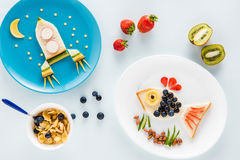 Delicious funny sandwiches on plates and cereal flakes with fruits Stock Photos