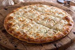Garlic Fingers Pizza. Delicious garlic fingers with herb butter and melted mozzarella cheese on a rustic wooden board stock images