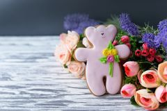 Delicious gingerbread cookie teddy bear with flowers on a wooden Stock Photo