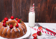 Delicious glazed cake with strawberry and bottle of milk Stock Image