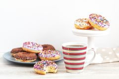 Delicious glazed donuts and cup of coffee on light wooden backgr stock photography