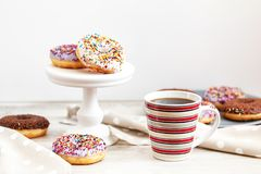 Delicious glazed donuts and cup of coffee on light wooden backgr royalty free stock photo