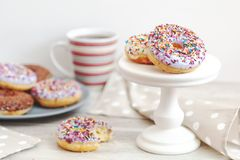 Delicious glazed donuts and cup of coffee on light wooden backgr royalty free stock images