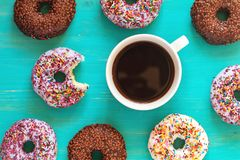 Delicious glazed donuts and cup of coffee on turquoise surface stock image